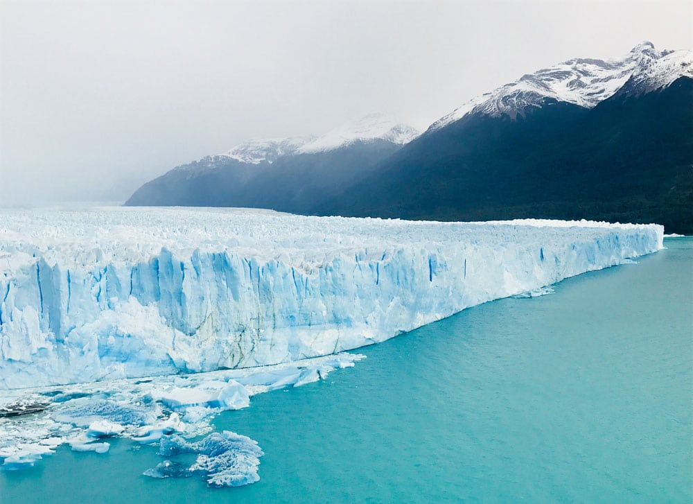 ice wall of glacier in turquoise blue water