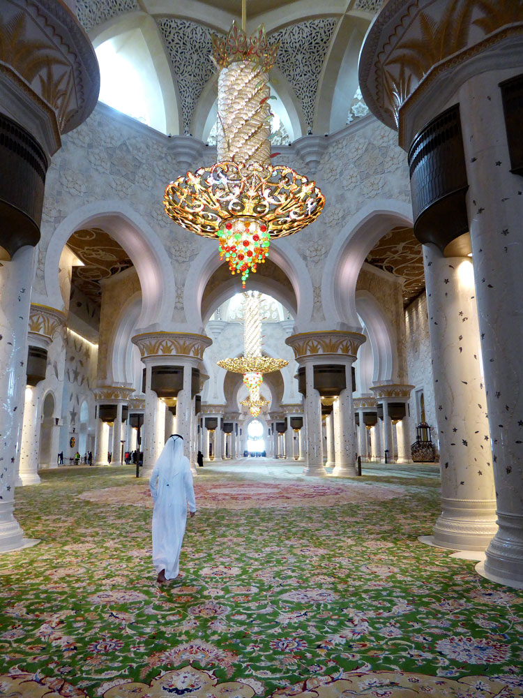 man walking across a carpet in a mosque