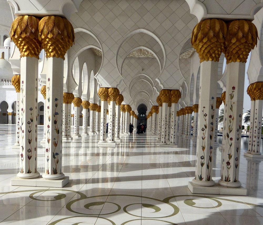 women walking between ornate pillars and marble floor of mosque