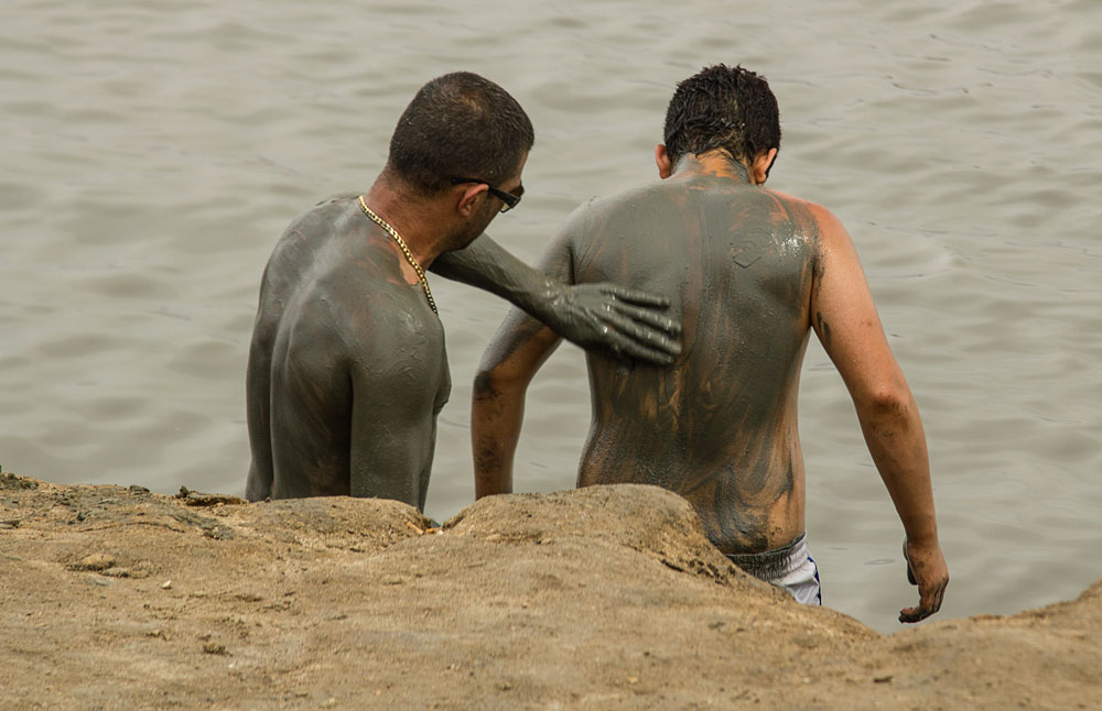 a man applying mud to another mans back at the dead sea