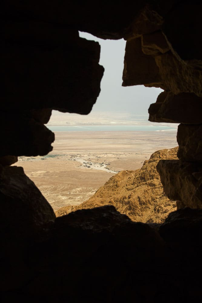 view of desert and dead sea through window in rock at masada