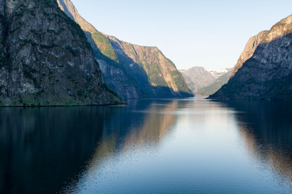 a fjord in norway with mountains reflected in water