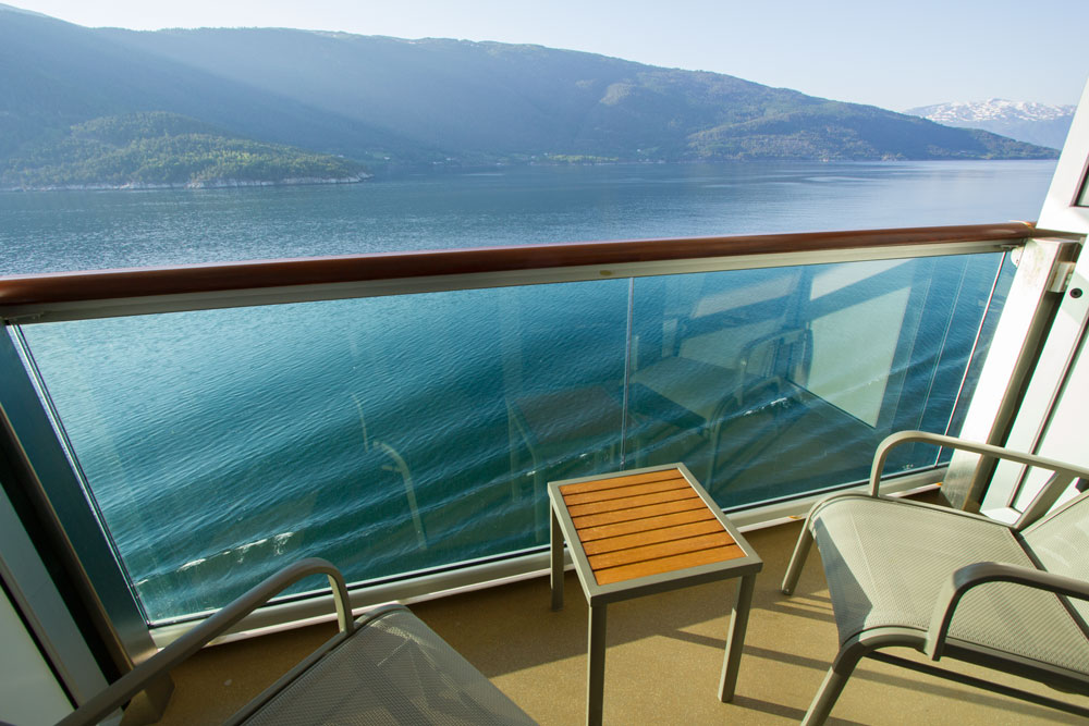 the balcony of a cruise ship cabin looking out to a norway fjord