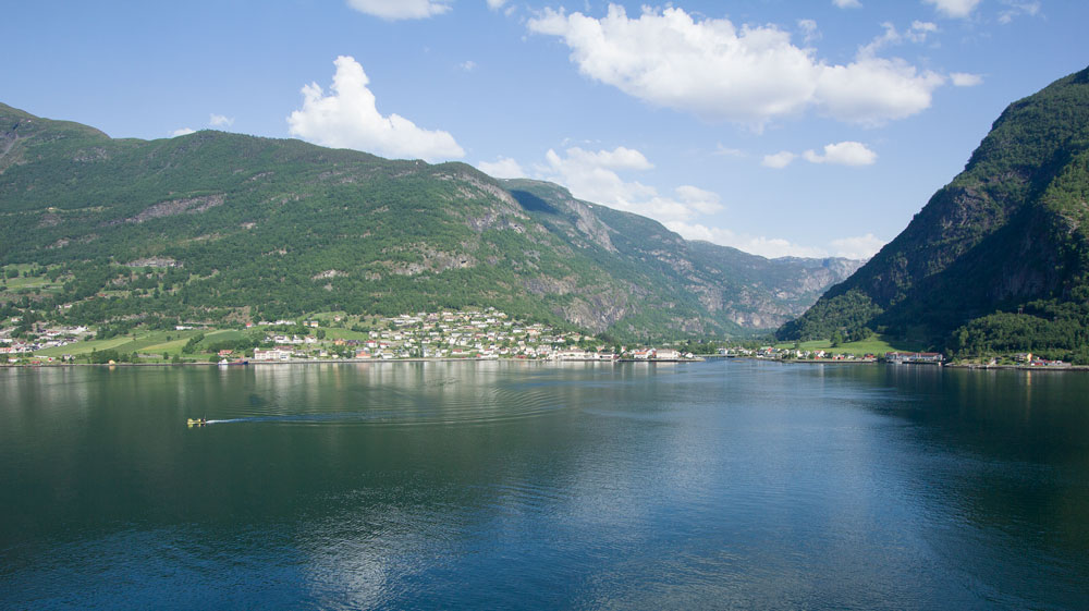 norwegian fjord with mountains reflected in water and blue sky