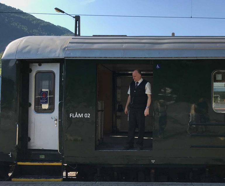 conductor standing in doorway of flam railway train