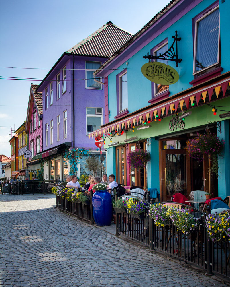 group of people having a coffee outside brightly coloured buildings in skagen stavanger