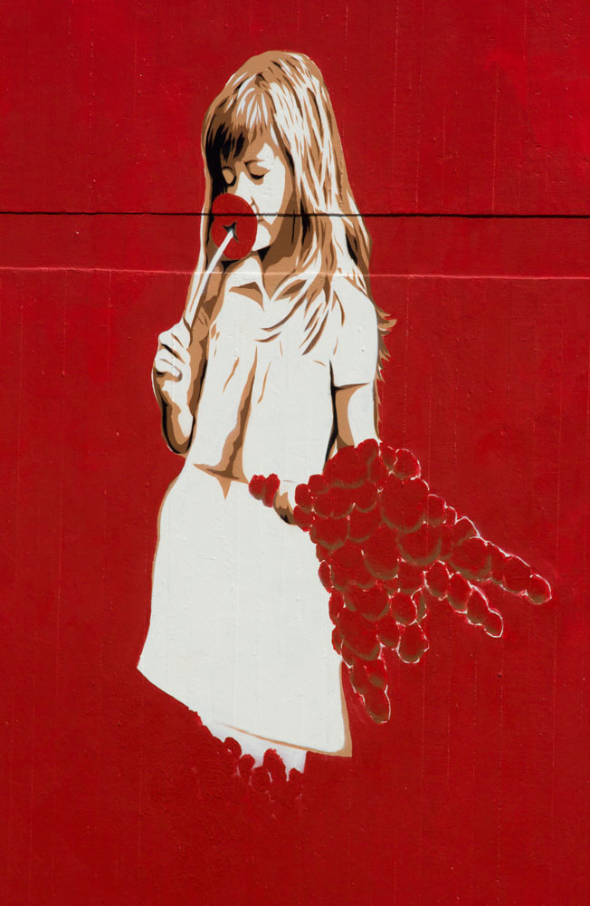 mural of gril in white derss smelling a red flower