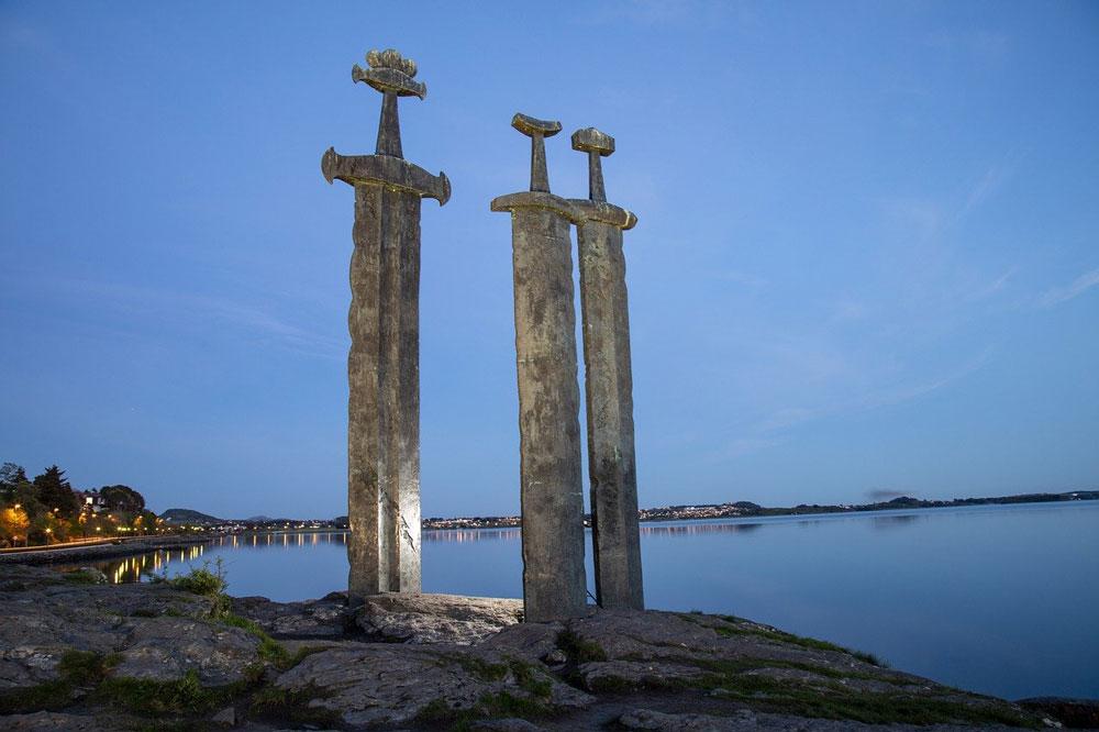 three massive swords anchored a rock