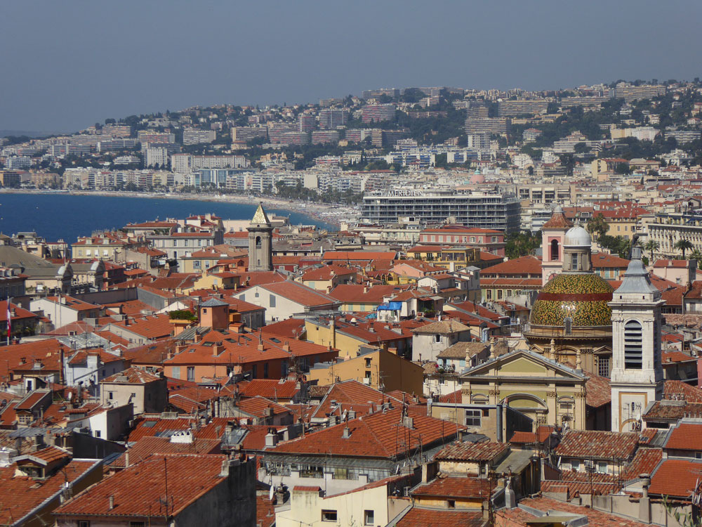 panoramic view of red rooftops and beach in nice france