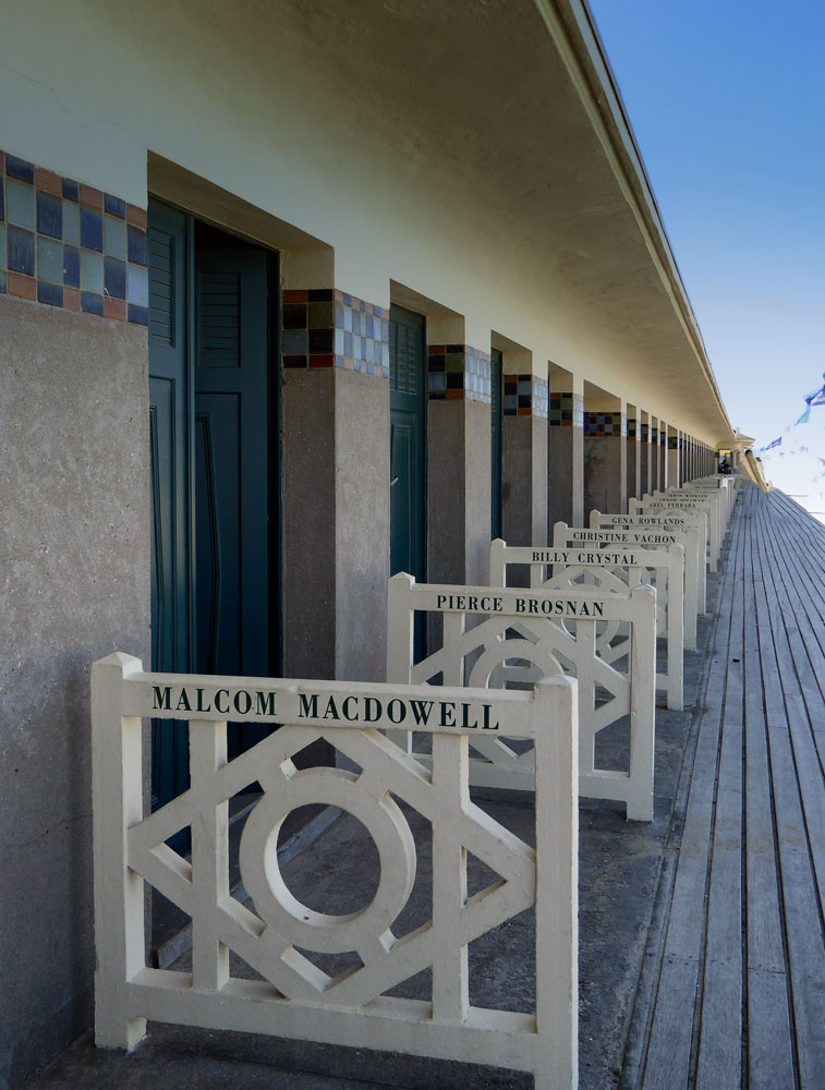 row of beach houses on wooden walkway each with name of someone in film industry in deauville normandy