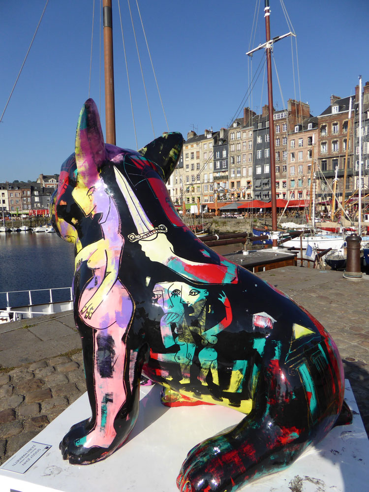 statue of huge painted cat overlooking harbour with boats and houses in honfleur normandy