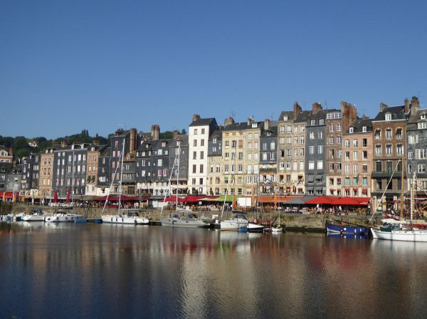 brightly coloured houses of honfleur normandy reflected in the water of the harbour