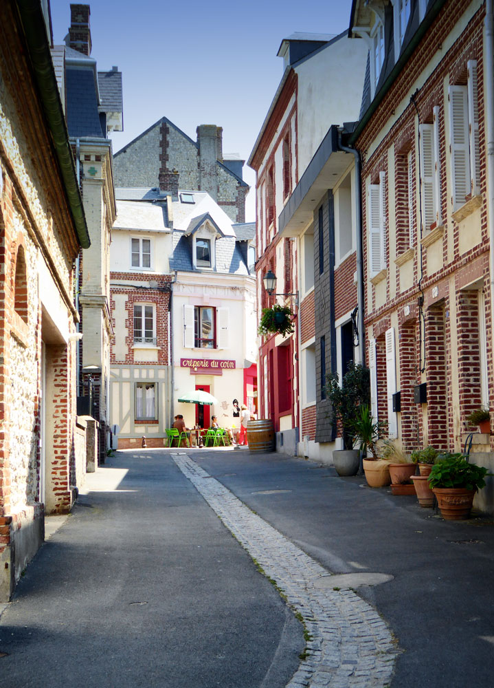 pretty cobblestoned street leading to people dining outside cafe
