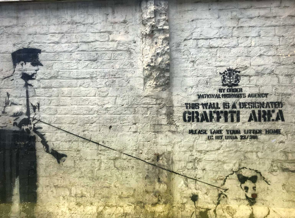 brick lane street art by banksy of security guard with dog
