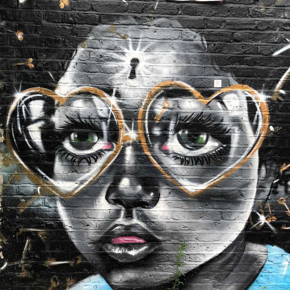 brick-lane-street-art-of young girl with heart shaped glasses