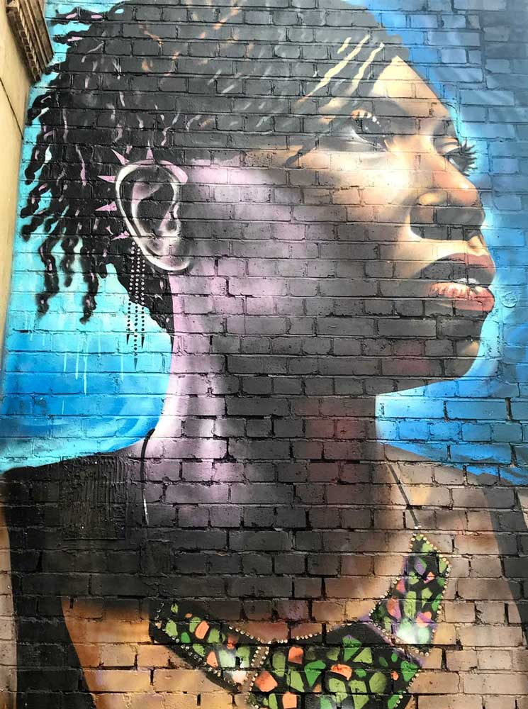 brick-lane-street-art-by-dreph of woman wearing brightly coloured african necklace