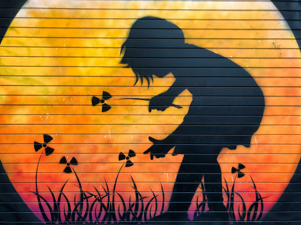 brick-lane-street-art-by-otto-schade of sillhouetted girl picking flowers