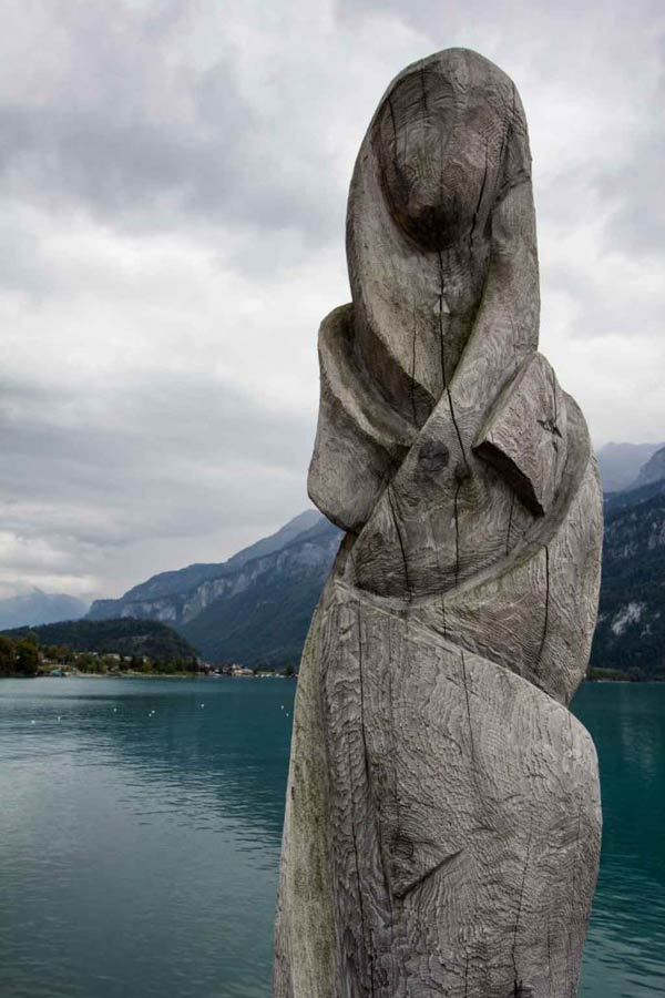 MODERN SCULPTURE OF PERSON BY LAKESIDE