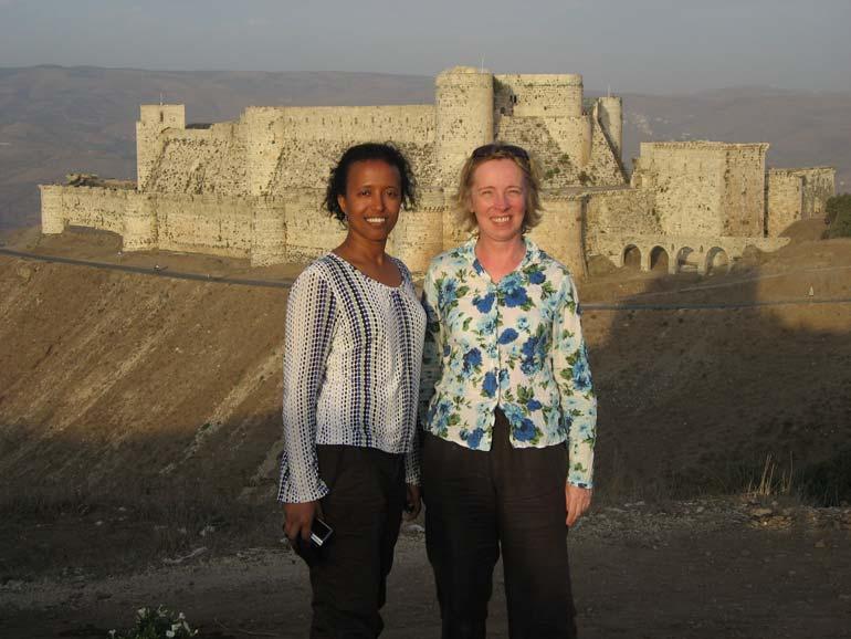 2 women standing in front of crusader castle  krak-des-chevaliers-syria