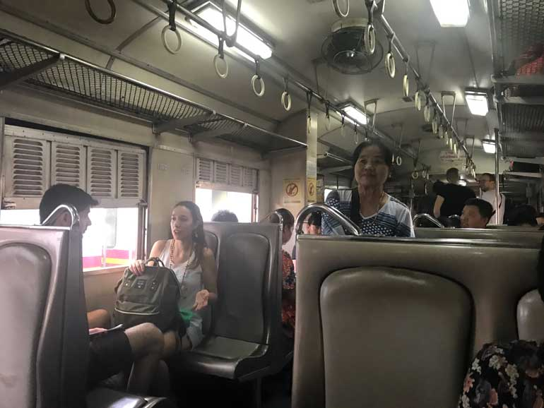 people sitting in a 3rd-class-thai-train