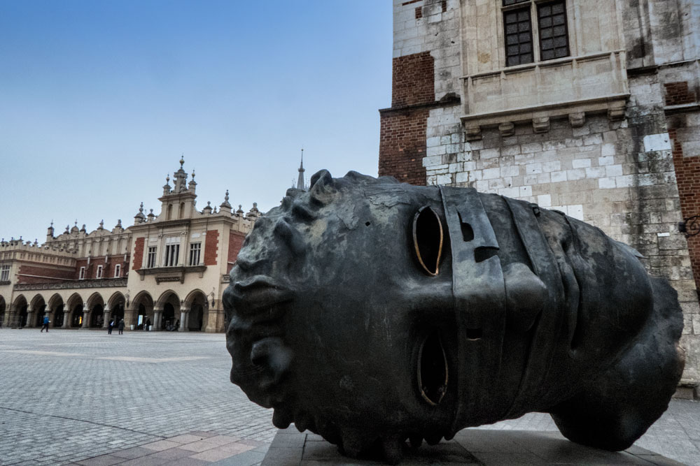 massive head sculpture in old square in krakow