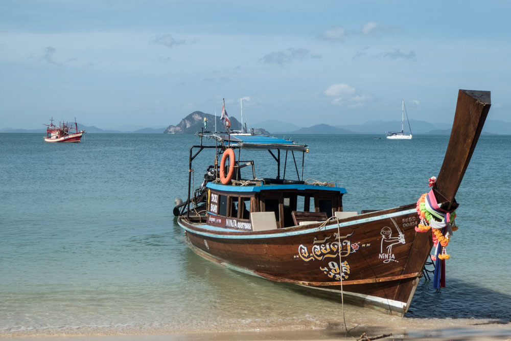 traditional Thai wooden fishing boat on sandy beach with blue water at koh yao yai