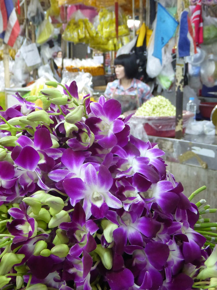 woman sitting behind purple flowers in market seen on a chao phraya boat tour