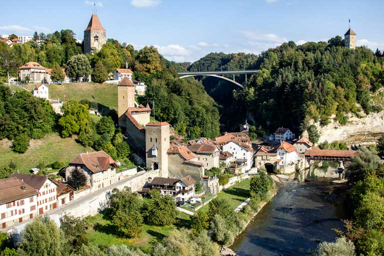 dramatic river gorge lined with buildings including a church