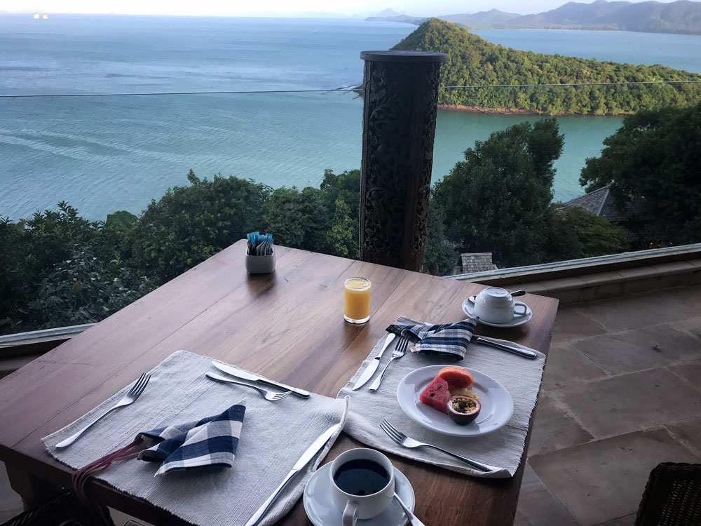 breakfast setting for one on terrace overlooking bay