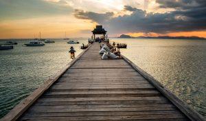 wooden pier reaching out to sea at sunset at santhiya-resort-koh-yao-yai