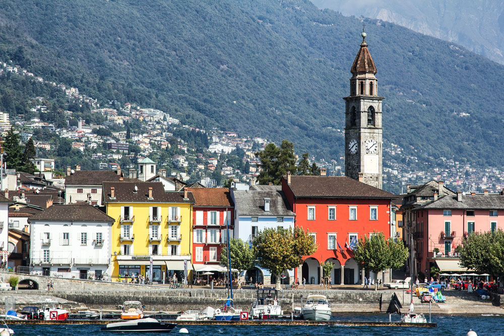 brightly coloured buildings and church along the shore at ascona