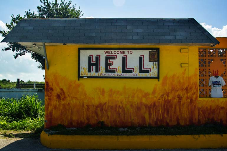 sign for the town of hell on wall of a building