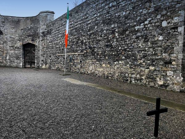 courtyard with stone walls and cross and tricolor flag at kilmainham gaol dublin