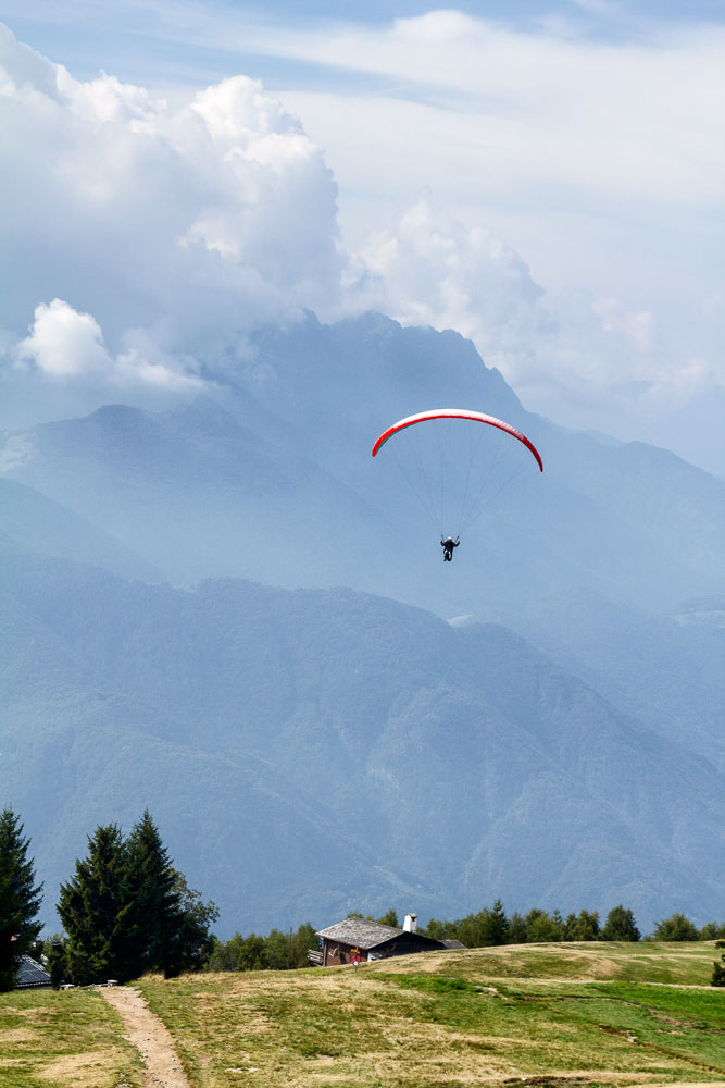 person paragliding over swiss mountain