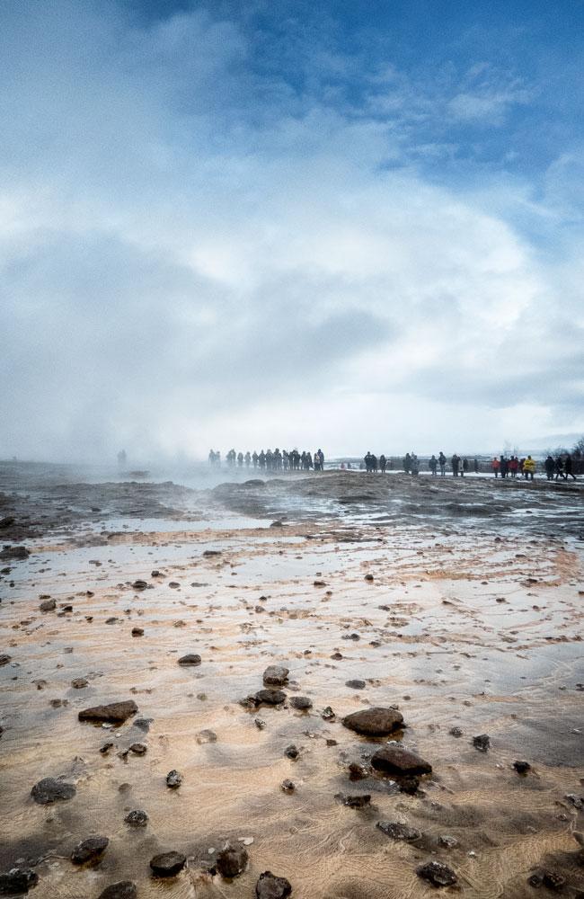 people walking through steaming lava field in geysir iceland