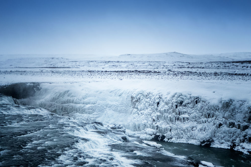 glacial water rushing through snow and ice covered landscape