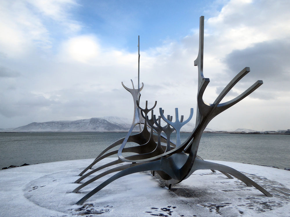 modern sculpture of viking boat by habour with snow topped mountain in background