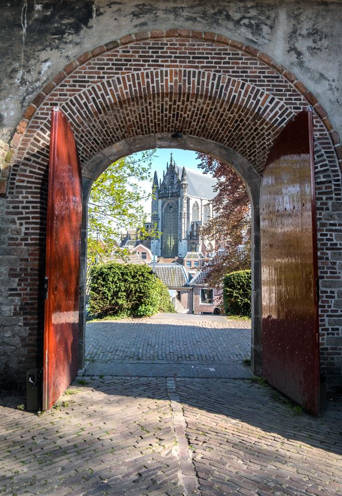 church seen through arched gateway in leiden