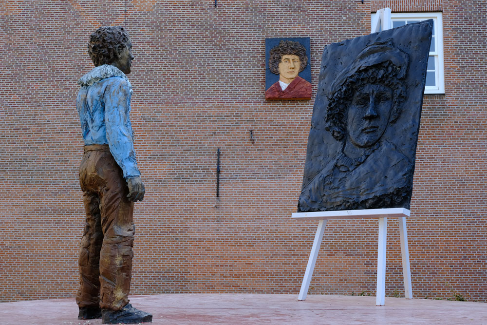 sculpture of young boy in front of an artist's easel