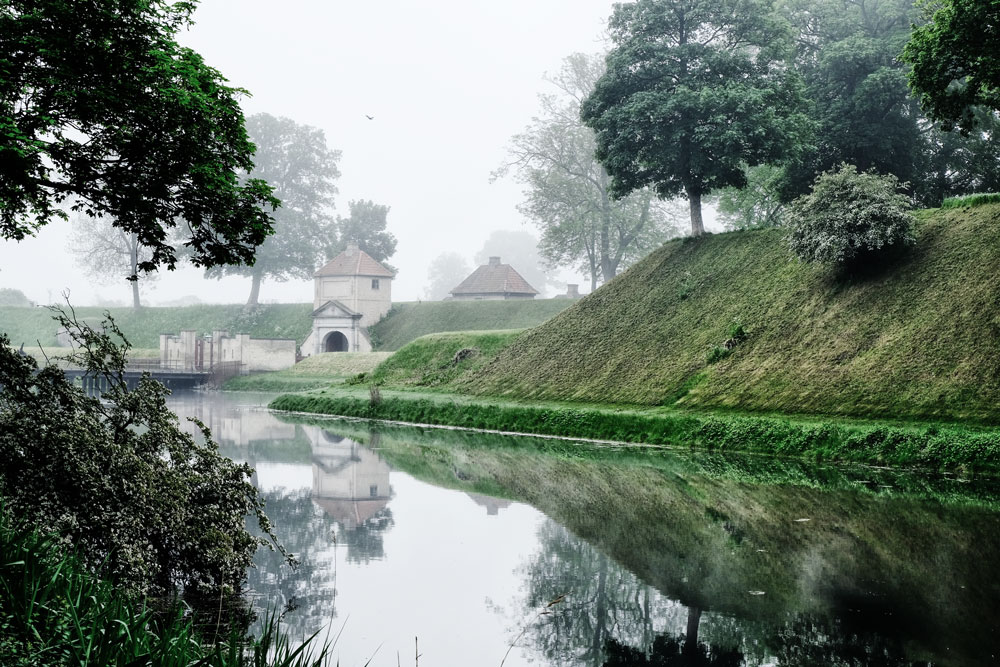 greenery and buidling reflected in water of moat