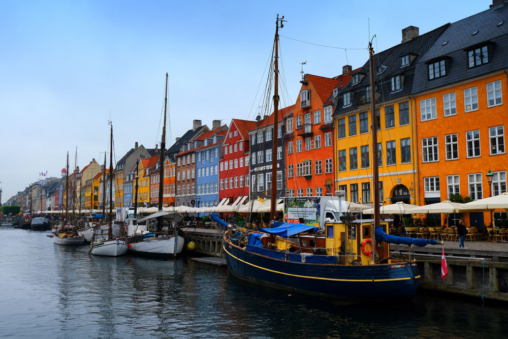 brightly coloured buildings along canal in copenhagen cruise stop