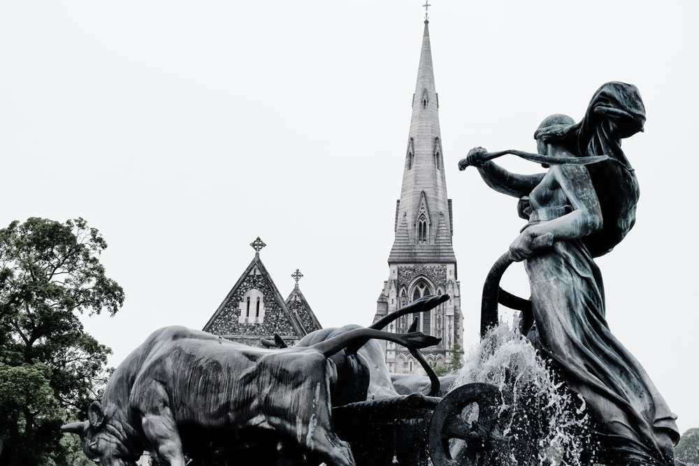 sculpture of woman and horse in fountain outside church