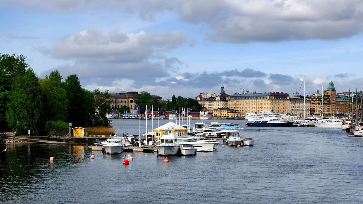 rover with boats and buildings on bank seen during one day in stockholm