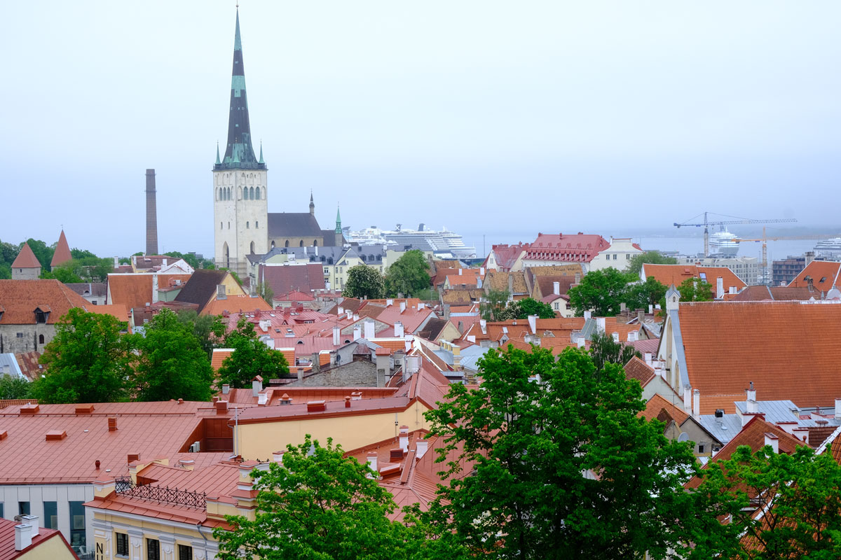 red roofs of tallinn with church spire and cruise ship in distance