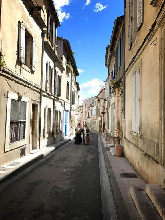 2 women in medieval costume walking along a narrow Arles street