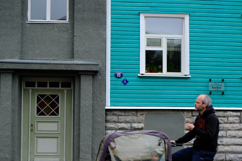 man riding bike with baby carrier past a teal coloured half timbered building