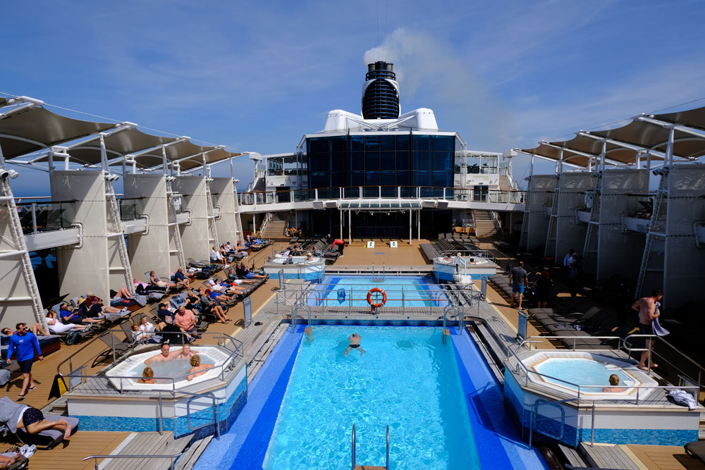 people swimming and relaxing around pool on the deck of a ship cruising around baltic capitals