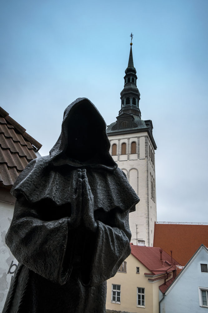 bronze statue of monk against the background of a church spire in tallinn estonia