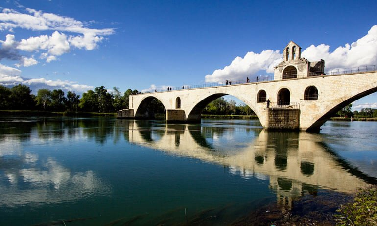 arched bridge reflected in still water in avignon-provence