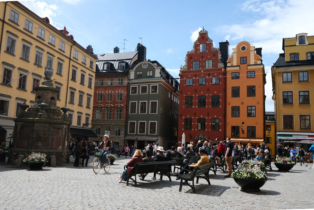 people sitting on benches in a cobblestoned square with gabled houses in stockholm